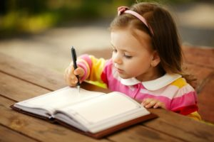 An image of a girl writing in a notebook - handwriting development