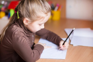 Young girl writing left handed