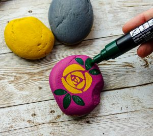 Decorate stones with flower designs